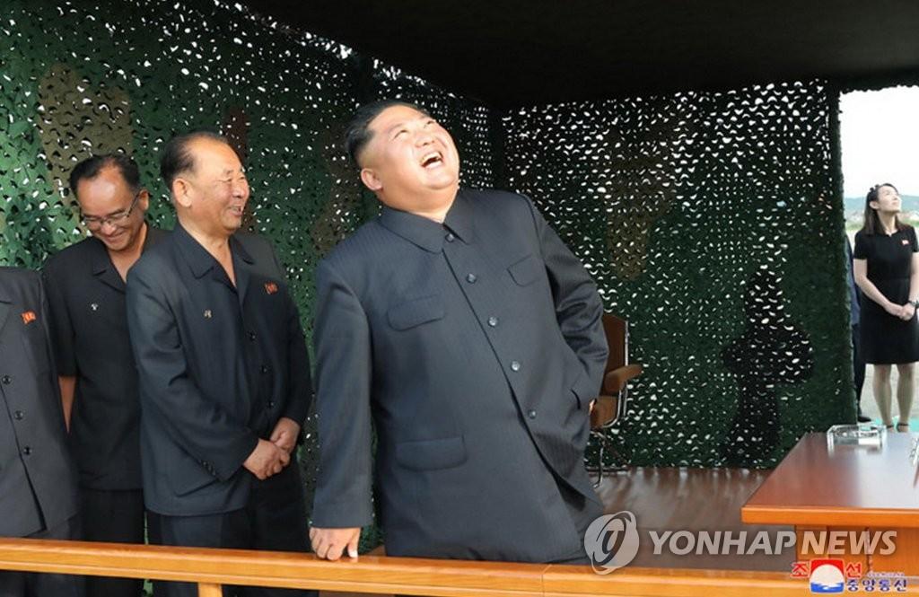 8月24日,金正恩笑看火箭炮飞天,胞妹金与正(右侧)陪同观摩。 韩联社/朝中社(图片仅限韩国国内使用,严禁转载复制)