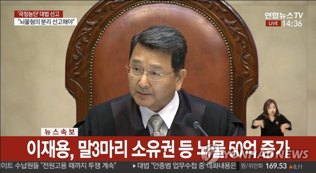 资料图片:大法官朴商玉宣读干政案判决。 韩联社TV截图(图片严禁转载复制)
