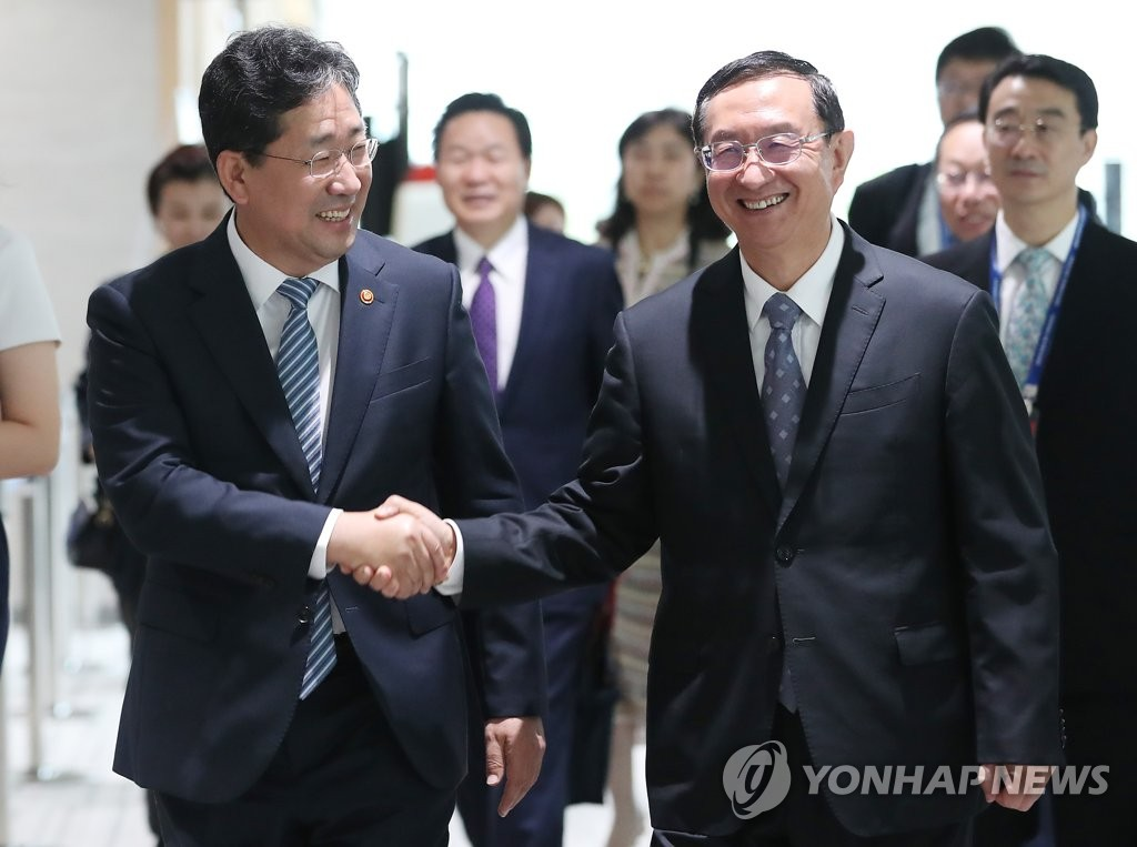 资料图片:8月29日,在仁川松岛,韩国文化体育观光部长官朴良雨(左)和中国文化和旅游部部长雒树刚在会前亲切握手。 韩联社