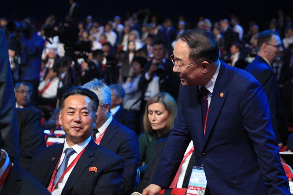 韩国副总理兼企划财政部长洪楠基(右)与朝鲜内阁副总理李龙男互致问候。韩联社