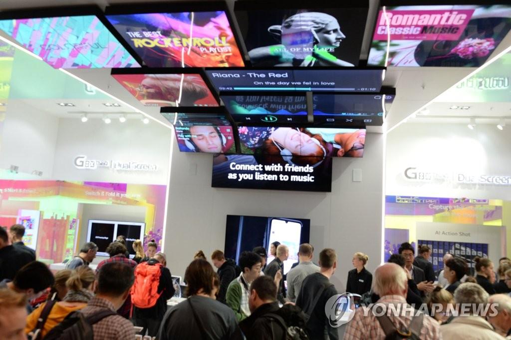 """资料图片:当地时间9月8日,在德国柏林国际电子消费品展览会(IFA)上,访客们在LG电子展台欣赏""""V50S ThinQ""""和双屏新品。 韩联社/LG电子供图(图片严禁转载复制)"""
