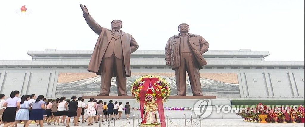 朝鲜民众向领袖铜像献花