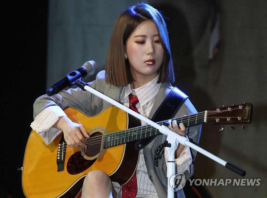 9月10日下午,在首尔,禹智润抱着吉他衔着拨片伴奏《工作狂》。 韩联社