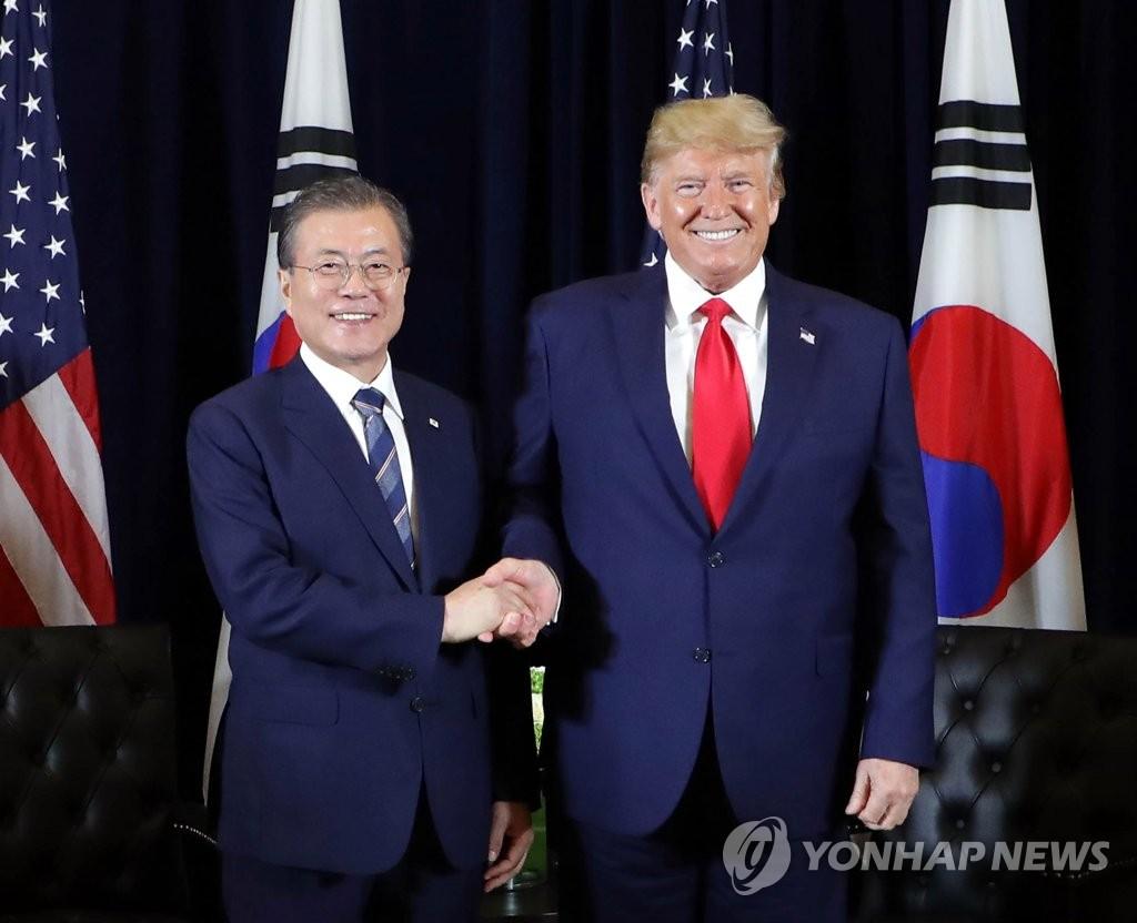 资料图片:当地时间9月23日,在纽约巴克莱洲际酒店,韩国总统文在寅(左)与美国总统特朗普在会谈开始前握手合影。 韩联社
