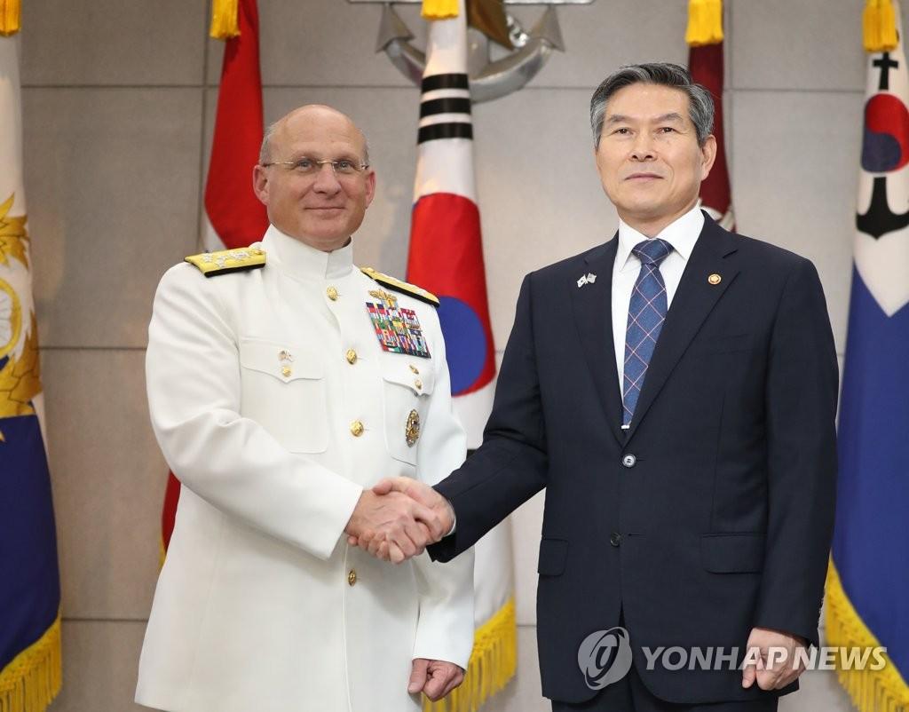 9月25日,在国防部,郑景斗(右)与迈克尔·吉尔迪握手合影。 韩联社
