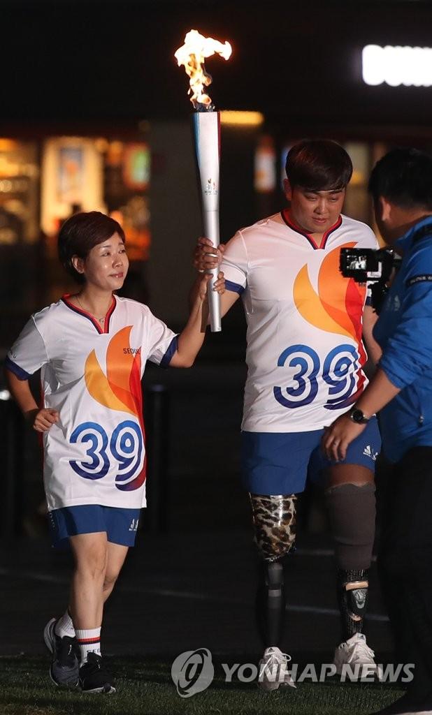 资料图片:第100届全国体育大会和第39届残疾人运动会圣火传递现场 韩联社