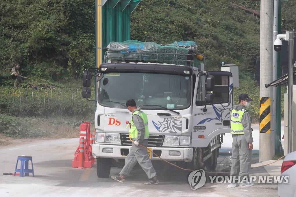 资料图片:10月1日,在京畿道坡州积城面,防疫部门正在对车辆进行消毒。 韩联社