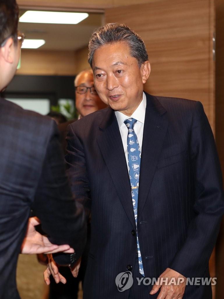 10月11日,在釜山金海机场,鸠山由纪夫与前来欢迎的釜山大学人士握手。 韩联社