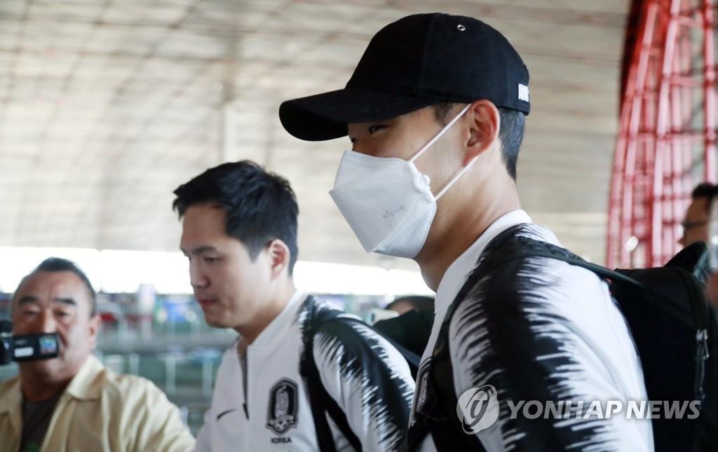 10月14日,韩国国脚孙兴慜(右)抵达北京首都国际机场。 韩联社