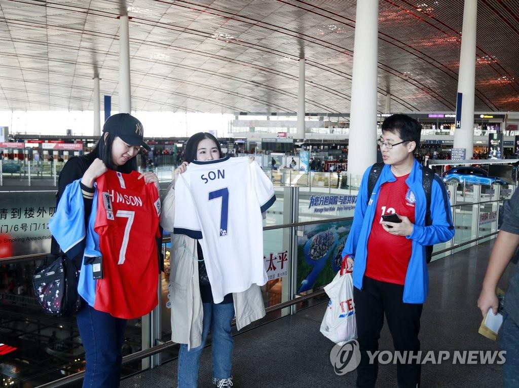 10月14日,在首都国际机场,中国球迷为韩国队加油。 韩联社