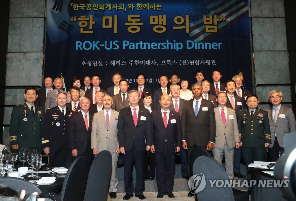 """10月17日下午,在首尔富拉泽酒店,美国驻韩大使哈里·哈里斯(前排左四)等有关人士出席""""韩美同盟之夜""""活动并合影留念。 韩联社"""