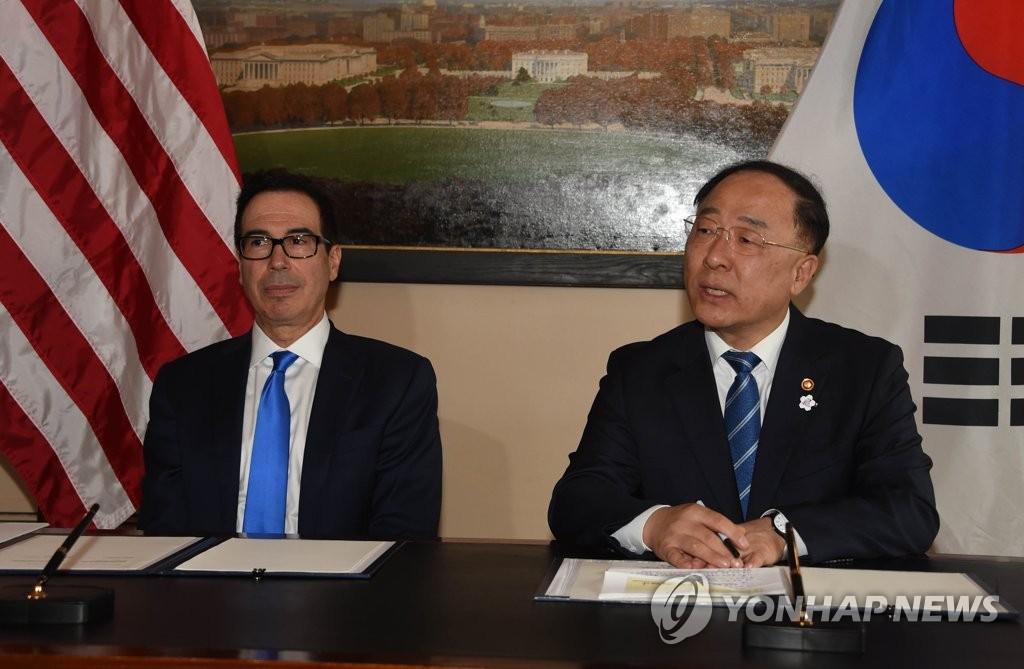 当地时间10月17日,在华盛顿,韩国副总理兼企划财政部长官洪楠基(右)与美国财政部长姆努钦举行会谈。 韩联社/企划财政部供图(图片严禁转载复制)