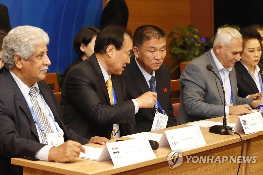 在亚洲举重联合会2019年会上,大韩举重联盟会长崔成龙(左二)和锦标赛组委会局长(左三)方文一对话。 韩联社/联合采访团(图片严禁转载复制)