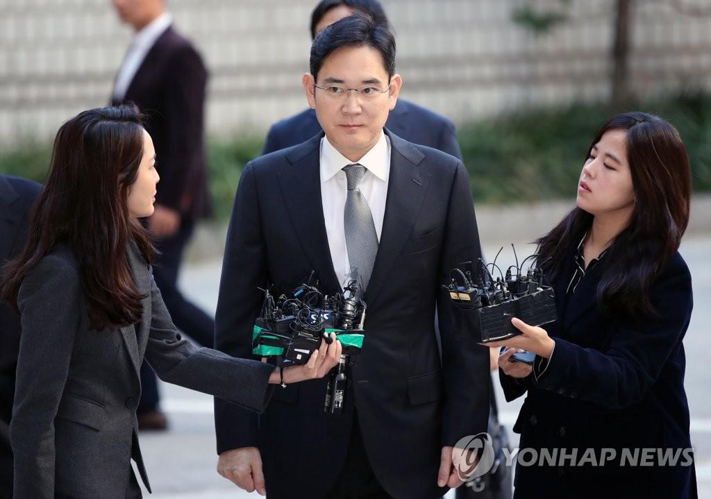 10月25日,李在镕(中)出庭前接受采访。 韩联社