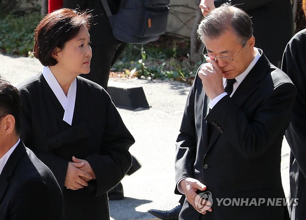 资料图片:10月31日,在釜山市水营区南川天主教堂,韩国总统文在寅(右)在母亲姜韩玉女士的出殡仪式上落泪。 韩联社