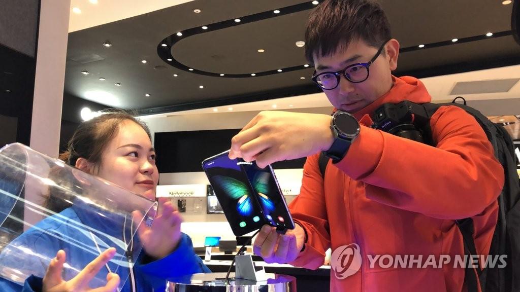 资料图片:11月8日,在上海南京东路三星旗舰店,一名顾客在试用三星折叠屏手机Galaxy Fold。 韩联社