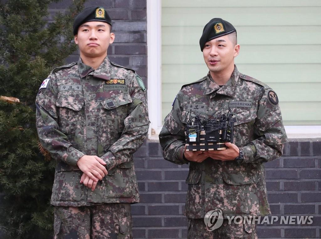 11月10日,在京畿道龙仁市地面作战司令部前,BIGBANG成员太阳(右)和大成答记者问。当天,二人正式退伍。 韩联社