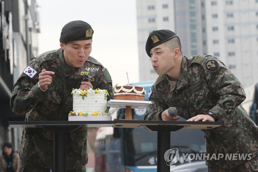 资料图片:2019年11月10日,BIGBANG成员太阳(右)和大成与粉丝庆祝退伍。 韩联社/YG娱乐供图(图片严禁转载复制)