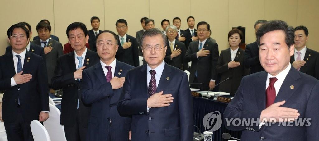 11月12日,在釜山会展中心,文在寅(前排右二)在国务会议前向国旗敬礼。 韩联社