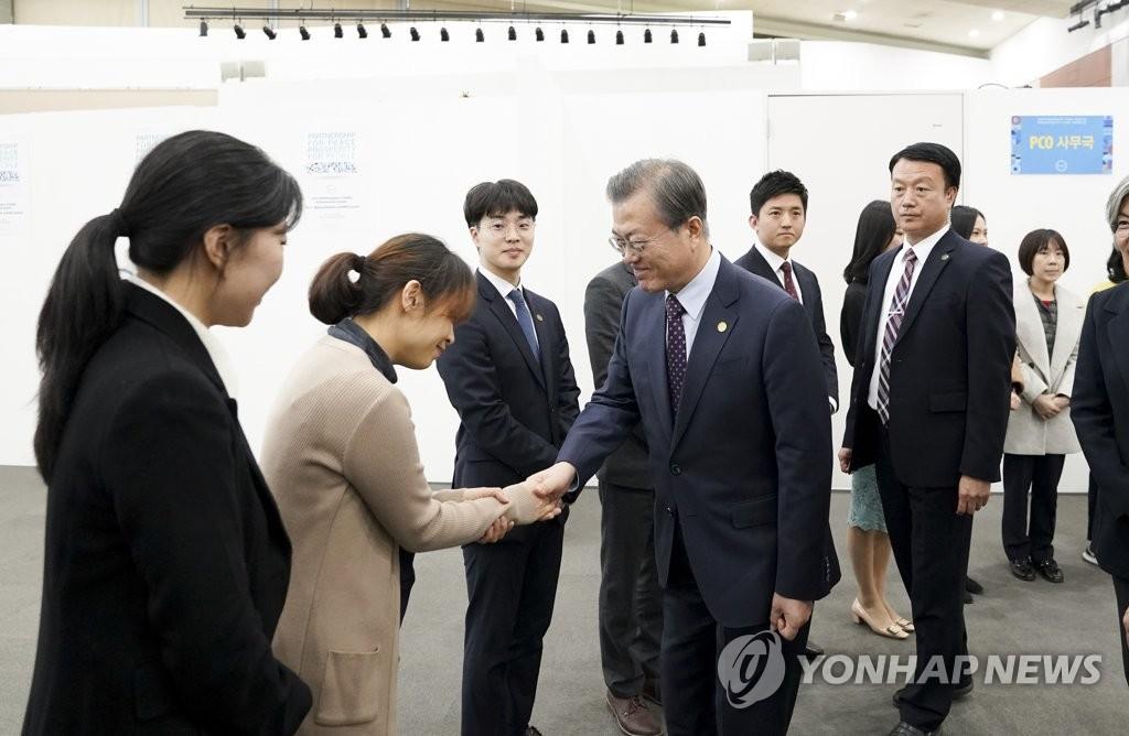 11月12日,在釜山会展中心,文在寅(右)与峰会筹划人员亲切握手。韩联社