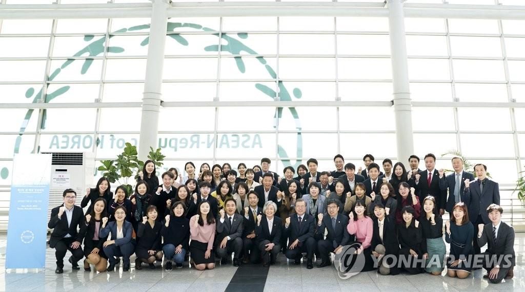 11月12日,在釜山会展中心,文在寅(前排居中)与峰会筹划人员合影留念。韩联社
