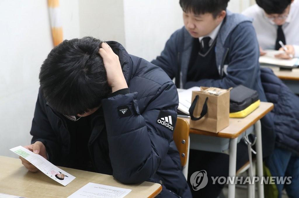 资料图片:11月13日,在首尔龙山高中,学生查看准考证。 韩联社