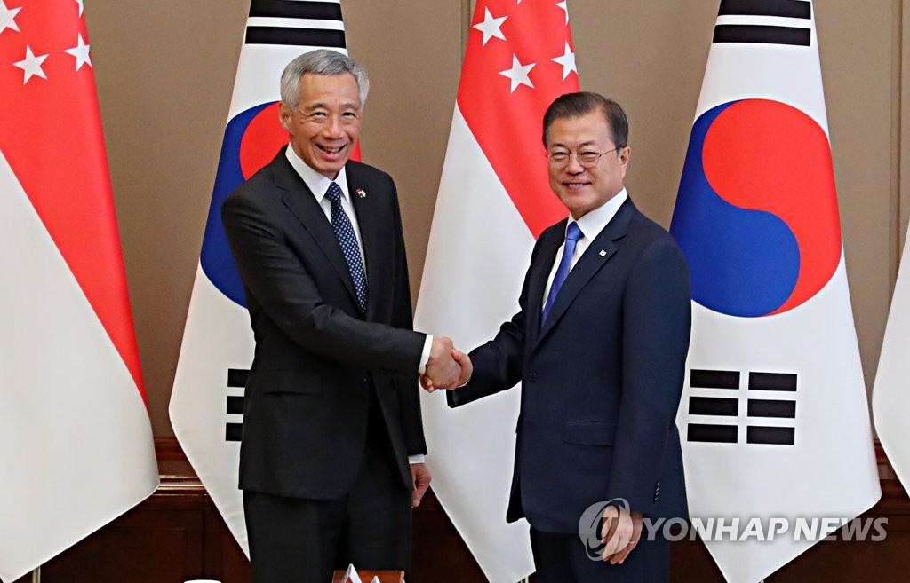 资料图片:11月23日,文在寅(右)与李显龙握手合影。 韩联社
