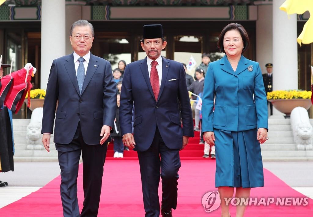 11月24日,在青瓦台,文在寅(左)和哈桑纳尔(中)走向欢迎宴会场。 韩联社