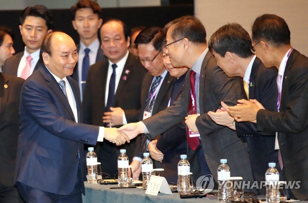 11月28日,在首尔君悦酒店举行的韩国与越南商务论坛上,越南总理阮春福(左)走入会场。 韩联社