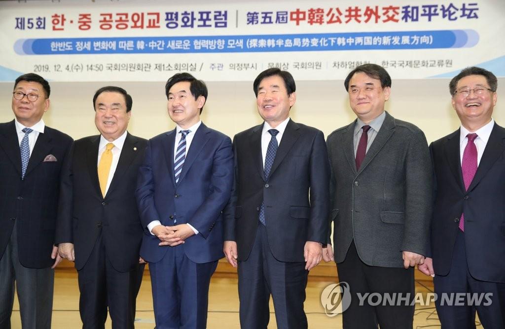 12月4日,在第五届韩中公共外交和平论坛上,文喜相(左二)同与会者合影。 韩联社