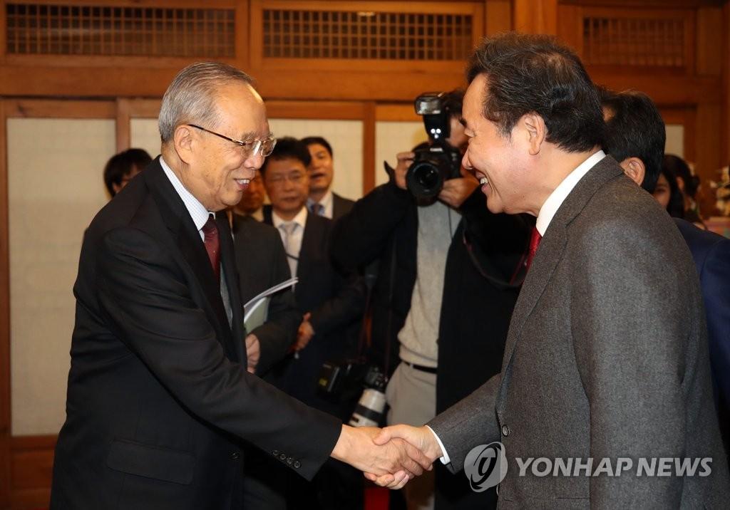 韩国国务总理李洛渊(右)和中国国际经济交流中心理事长曾培炎亲切握手。 韩联社