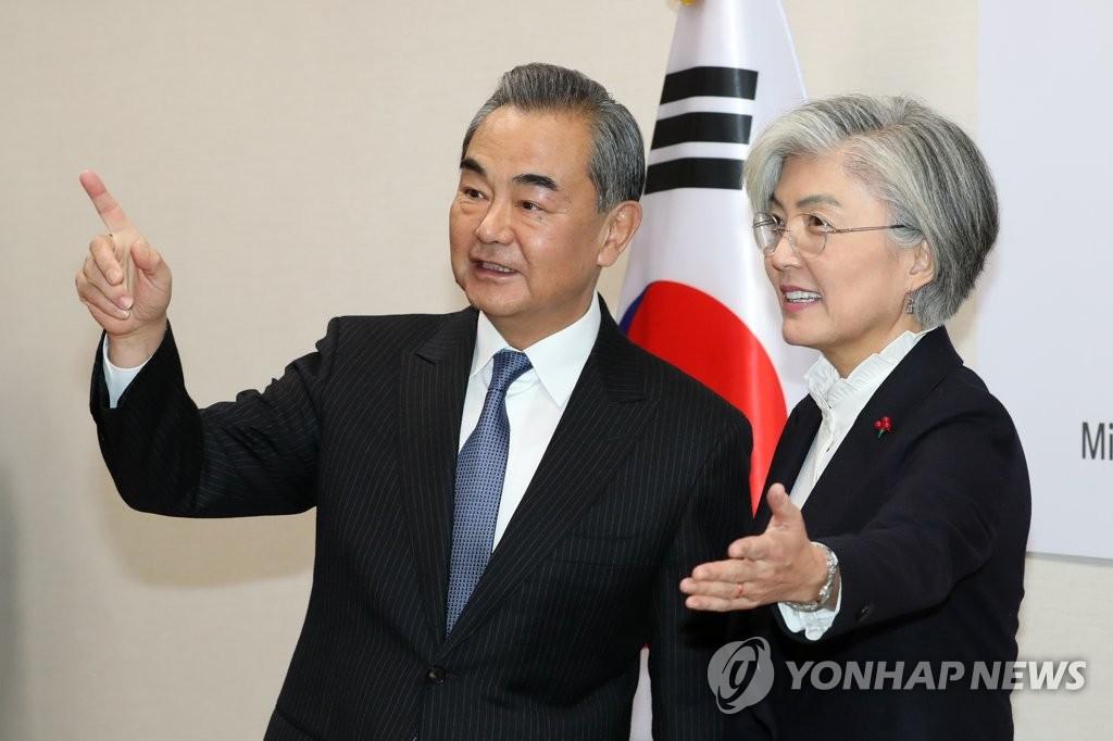 12月4日,在位于首尔的韩国外交部大楼,韩国外交部长官康京和(右)与到访的中国国务委员兼外交部长王毅亲切交谈。 韩联社