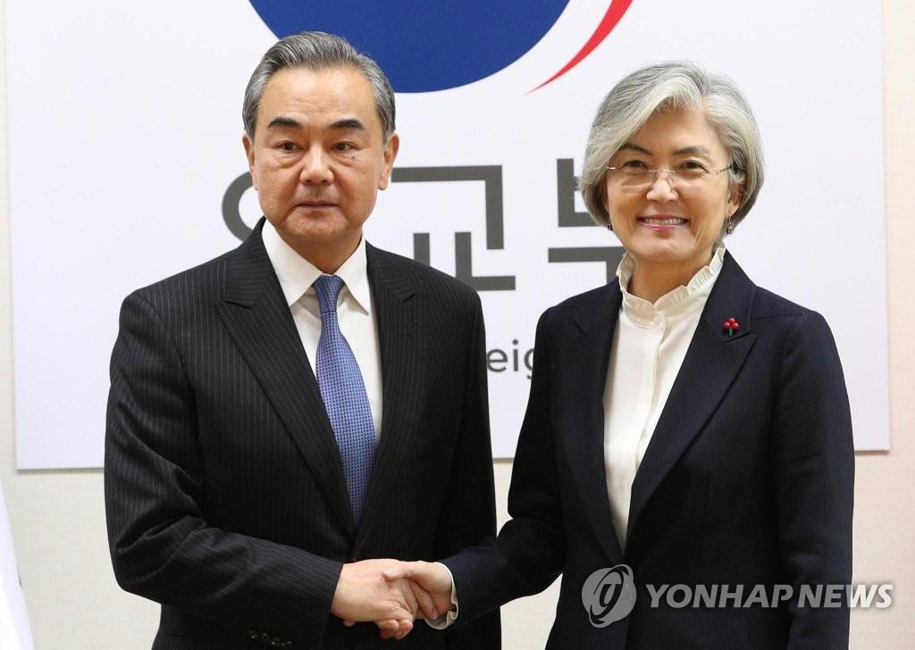 12月4日,在首尔市钟路区的韩国外交部,康京和(右)与王毅握手合影。 韩联社
