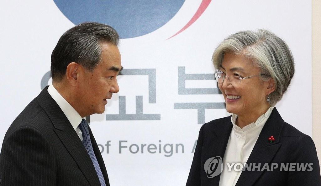 资料图片:康京和(右)和王毅 韩联社