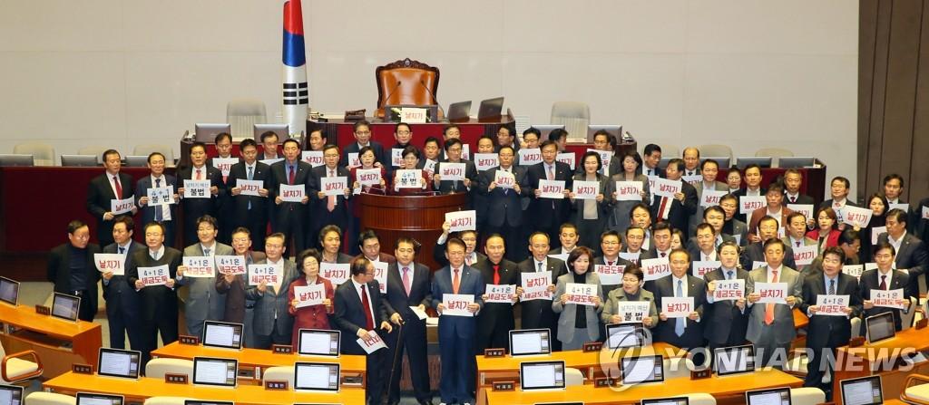 资料图片:12月10日,自由韩国党议员手举牌子,对明年度预算案获得通过表示抗议。 韩联社
