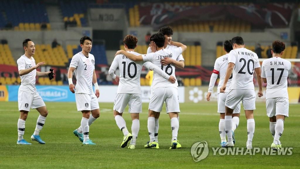 12月11日下午,在釜山亚运会主体育场举行的东亚足球锦标赛韩国和香港比赛中,黄仁范进球后与队友庆祝。 韩联社