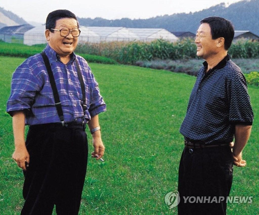 资料图片:LG集团第二任会长具滋暻(左)和长子具本茂(已故)交谈旧照 韩联社