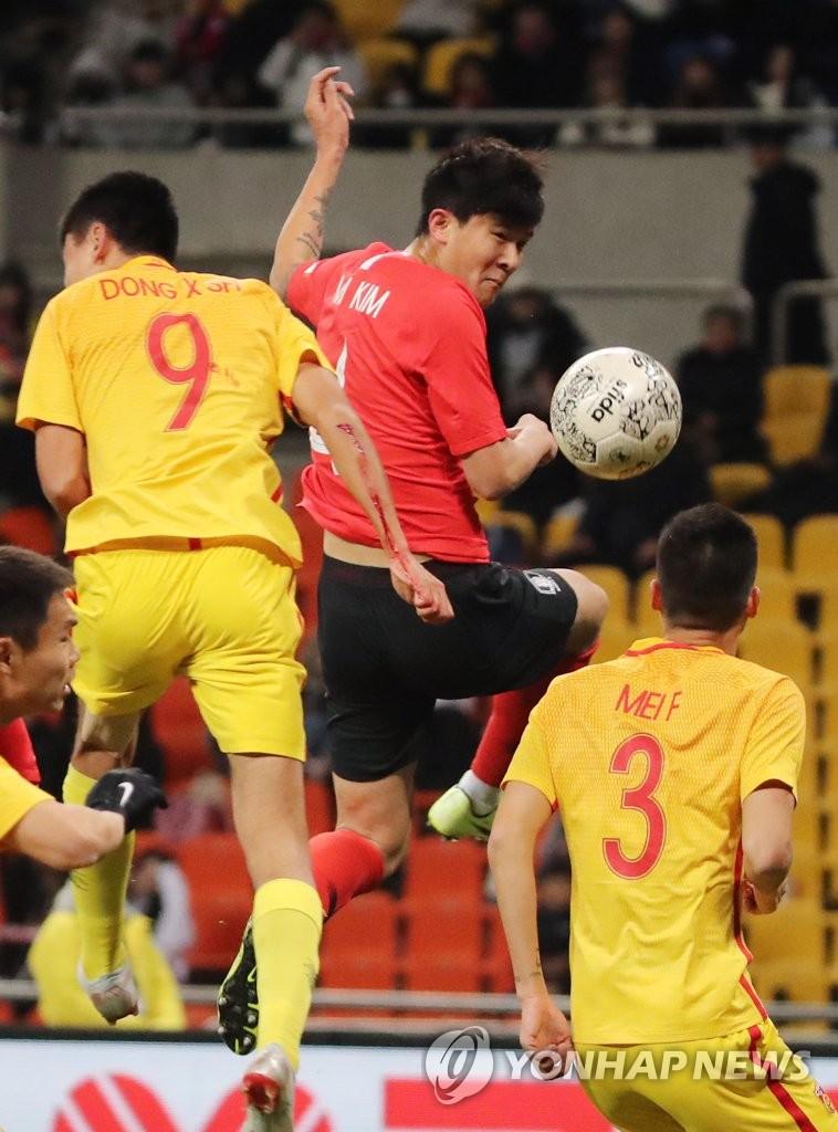 12月15日,在釜山亚运会主体育场举行的2019东亚足球锦标赛(东亚杯)韩国队迎战中国队的比赛中,金玟哉(红衣)头球攻门。 韩联社