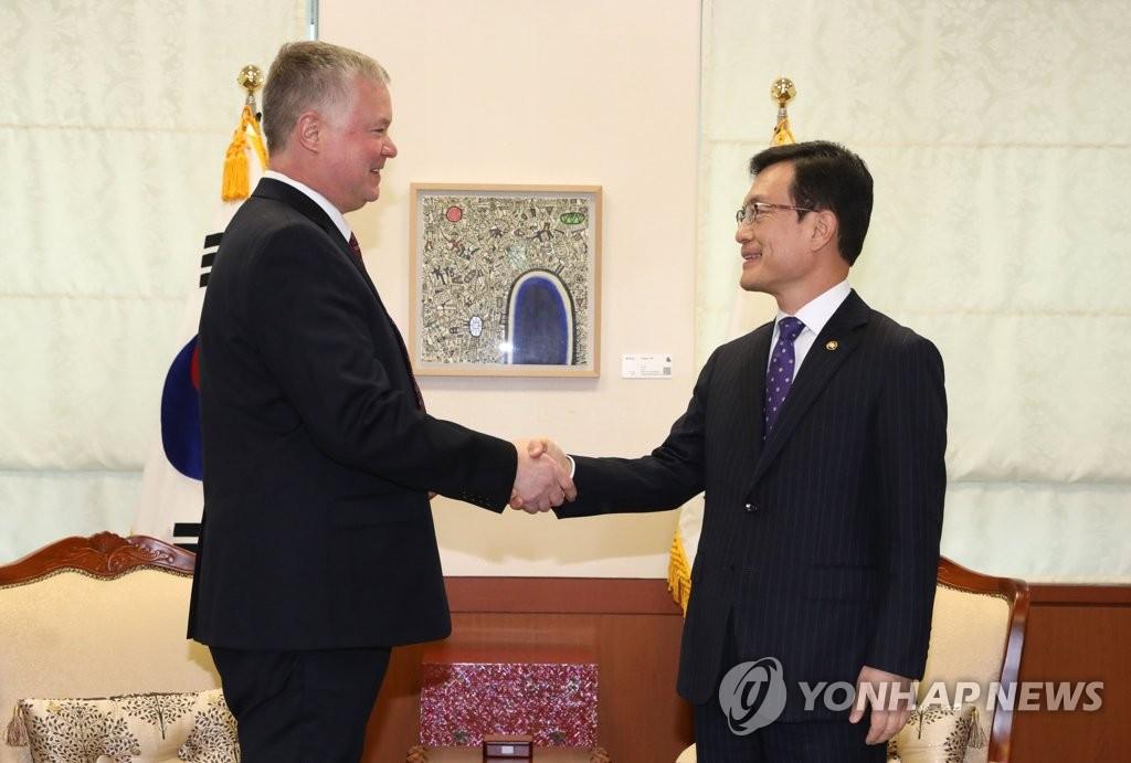 12月16日,在外交部大楼,比根(左)与赵世暎握手合影。 韩联社