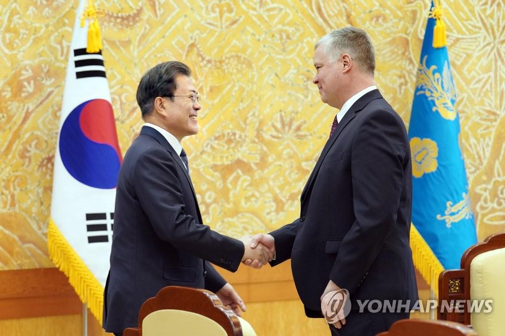 12月16日,在青瓦台,文在寅(左)与比根握手。 韩联社