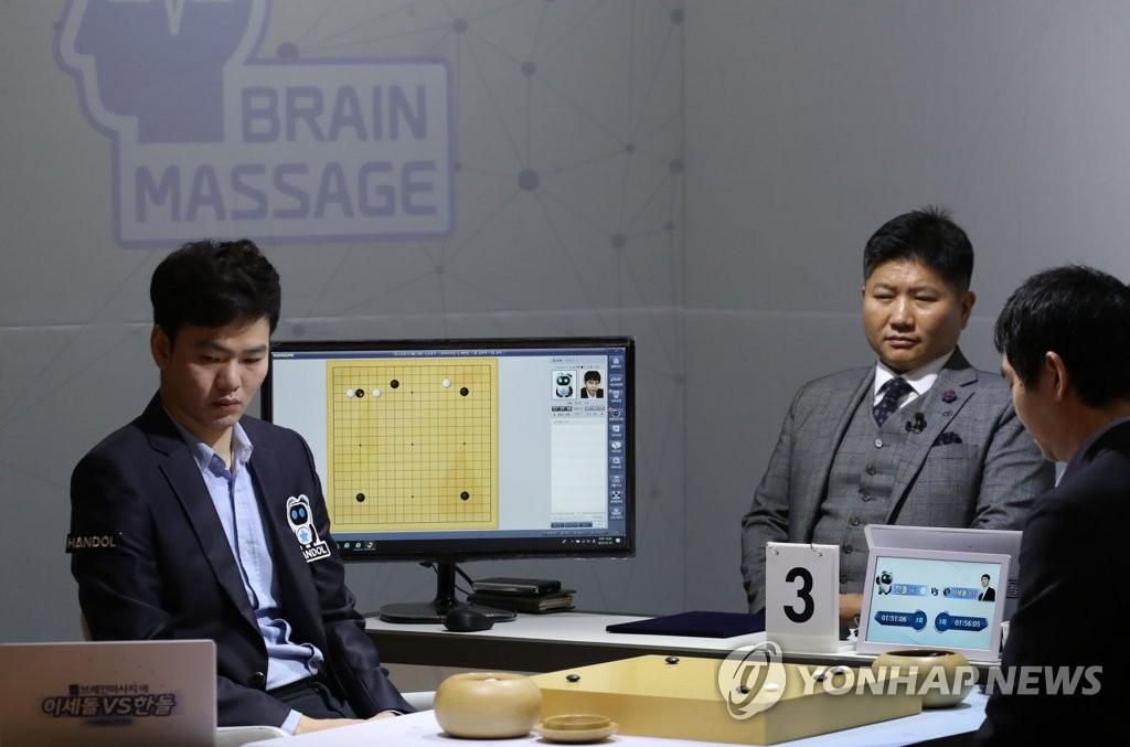 """12月18日,在按摩椅厂商Bodyfriend总部,研发人工智能围棋程序""""韩豆""""的NHN公司员工李和燮(音译)与李世石对坐(右)替""""韩豆""""落子。李和燮曾是韩国棋院研究生,棋力达到业务五段水平。 韩联社"""