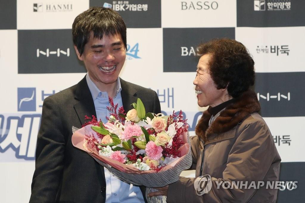 资料图片:12月21日,李世石(左)接过母亲送的花束。 韩联社