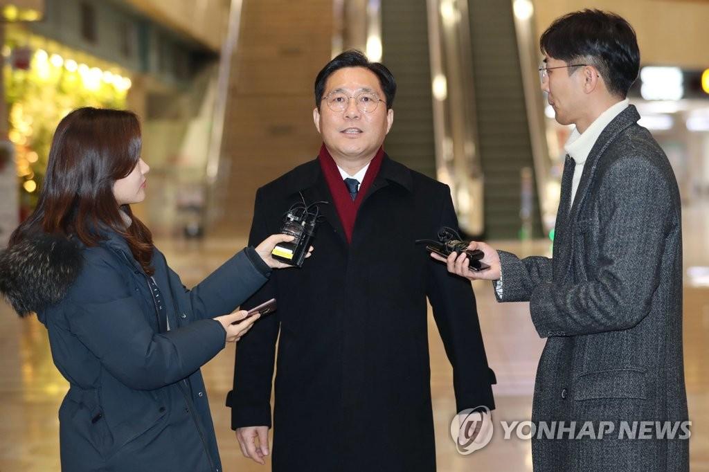 资料图片:12月22日,在金浦机场,韩国产业部长官成允模(中)接受媒体采访。 韩联社