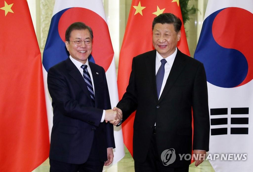 2019年12月23日,在北京人民大会堂,韩国总统文在寅(左)与中国国家主席习近平握手合影。 韩联社