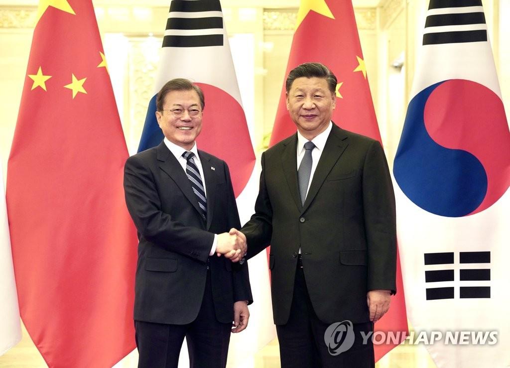 资料图片:12月23日,在北京,文在寅(左)和习近平握手合影。 韩联社