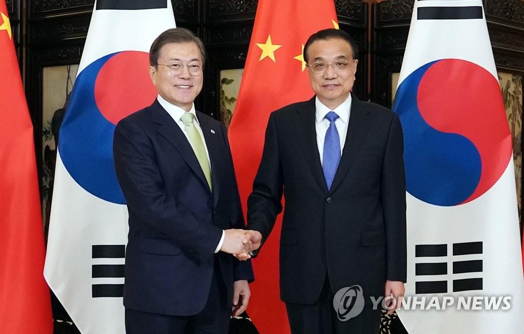 资料图片:韩国总统文在寅(左)与中国国务院总理李克强 韩联社