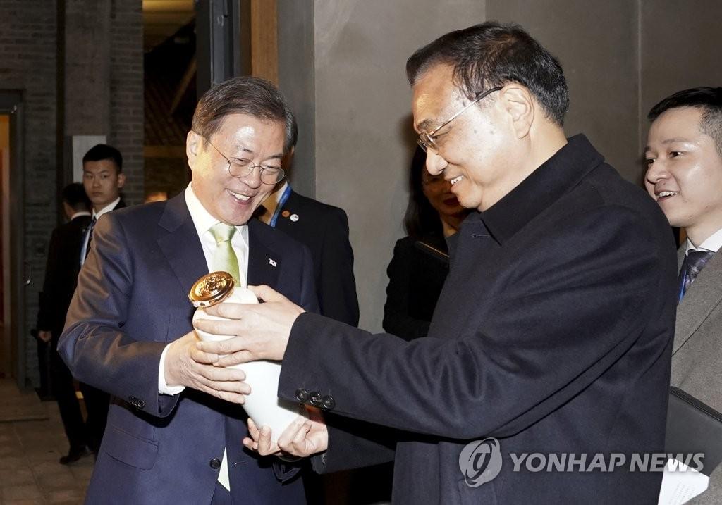 12月23日,在成都水井坊博物馆,韩国总统文在寅(左)接过中国国务院总理李克强赠送的一瓶特酿酒。 韩联社