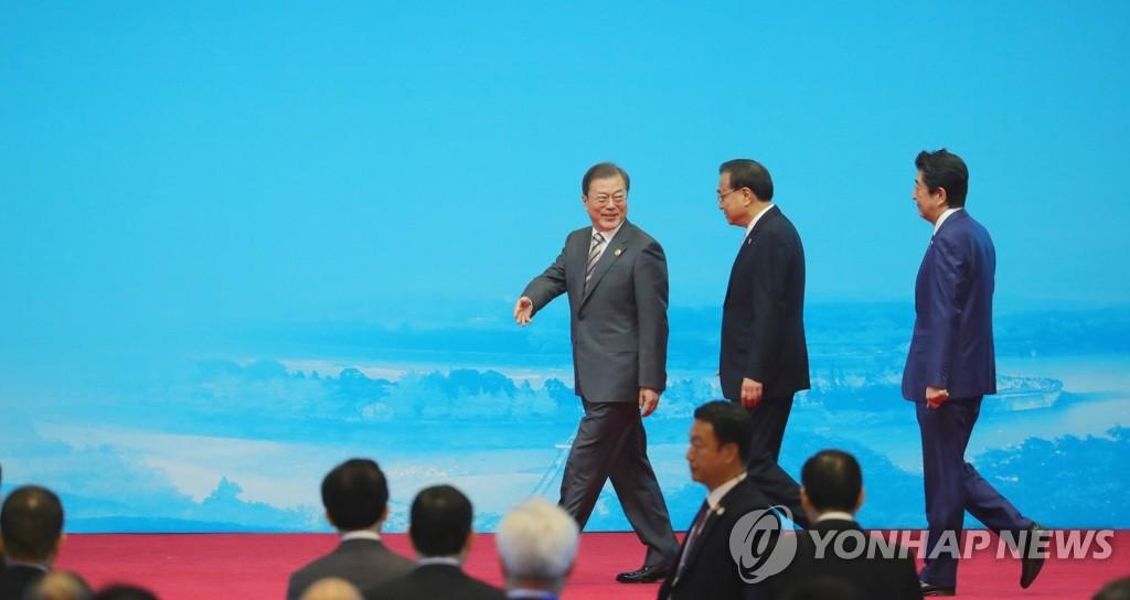 12月24日,在成都世纪城新国际会展中心,韩国总统文在寅(左)、中国国务院总理李克强(中)和日本首相安倍晋三步入工商峰会会场。 韩联社