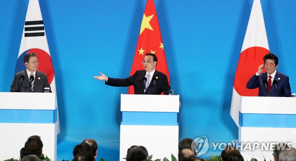 资料图片:12月24日,在成都,韩国总统文在寅(左起)与中国国务院总理李克强、日本首相安倍晋三共同会见记者。 韩联社