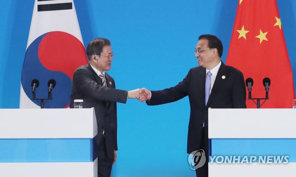 资料图片:12月24日,在成都世纪城新国际会展中心,韩国总统文在寅(左)和中国国务院总理李克强在第八次韩中日领导人会议记者会上握手。 韩联社